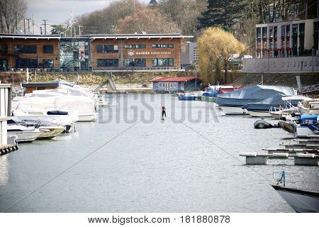 MAINZ, GERMANY - FEBRUARY 23: A stand up paddler paddles along the inland harbor at the Victor-Hugo-shore with motor boats and small yachts on February 23 2017 in Mainz.