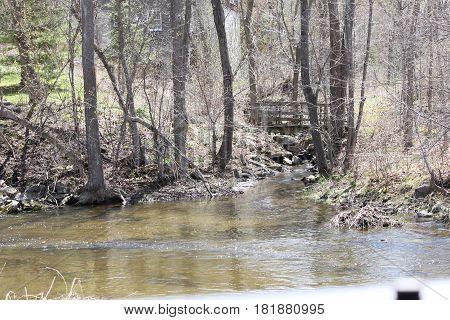 Little wooden walk bridge spanning a deep crevice full of rocks, water, early spring season.