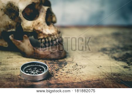 Pirate Skull and compass on vintage map with copy space