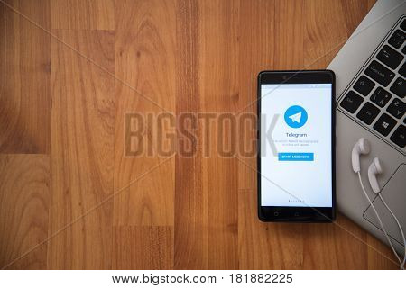 Los Angeles, USA, april 16, 2017: Telegram application on smartphone with earphones and notebook on wooden background.