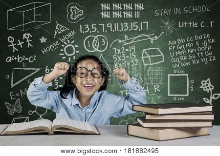 Successful student lifting her hands while sitting in front of book with doodle in classroom