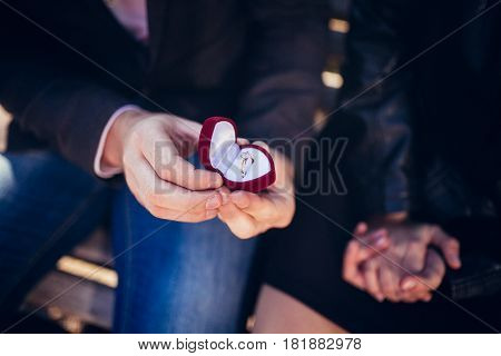 Proposal. Man's Hands Are Holding A Red Gift Box With A Ring.