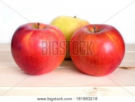 Three big ripe red apples in beige wooden shelf on white background front view closeup