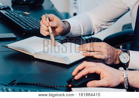 A Male Hand Is Writing In A Big Notepad On A Wooden Table