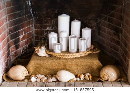 decorative fireplace with candles and many seashells