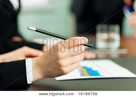 Business - meeting in an office; the businesspeople are discussing a document; close-up on hand