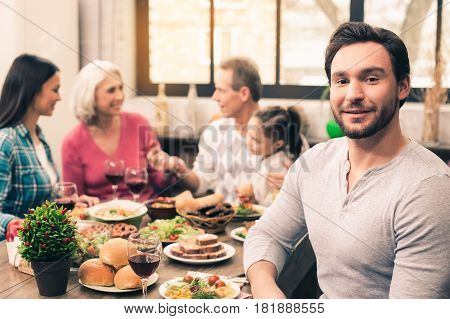 Family dinner. Beautiful family of five having meal. Tasty food on table. Happy family enjoying time together. Focus on young man. He smiling and looking at camera