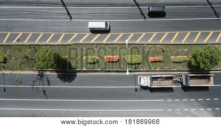 Aerial view of the wide road with a nice dividing strip of grass flowers and trees. Top view of moving cars and trucks Flat illustration of road traffic.