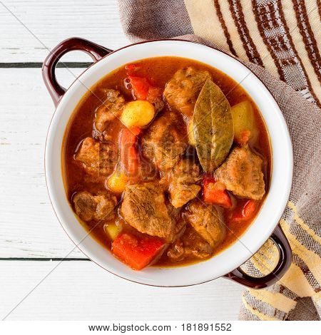 Goulash in ceramic bowl on white wooden background. Traditional hungarian soup. Rustic style. Top view.