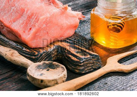 Uncooked pork meat loin on rustic wooden cutting board and honey in glass jar on old dark wood table. Close-up angle view