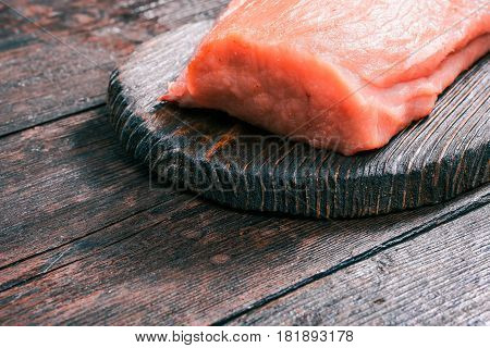 Raw pork meat loin on rustic wooden cutting board on old dark wood table. Close-up angle view