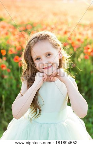 girl model, poppies, childhood, fashion, children, nature and summer concept - smiling beautiful little girl model is on the field of poppies in a blue ball dress , her hands supporting the chin