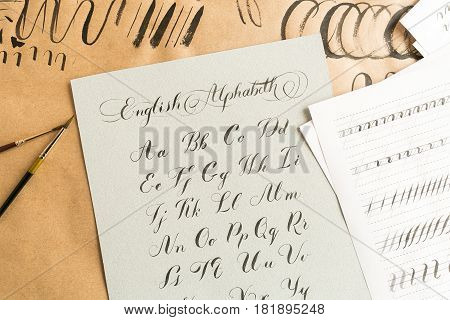 Hand drawn latin calligraphy of brush script. Letters of the alphabet written with a paint brush. Caligraphy, hobby, education concept. top view, flat lay.