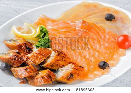Salmon fillet pieces conger eel sturgeon pieces served with lemon black olives herbs and cherry tomato on white plate close up with selective focus.