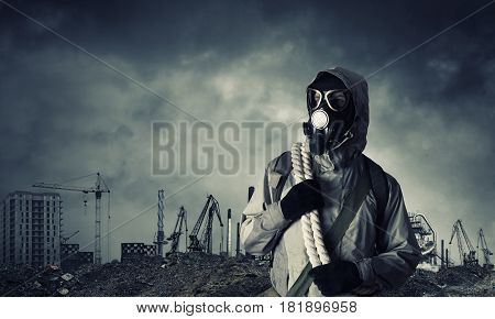 Man survivor in gas mask on industrial gray background