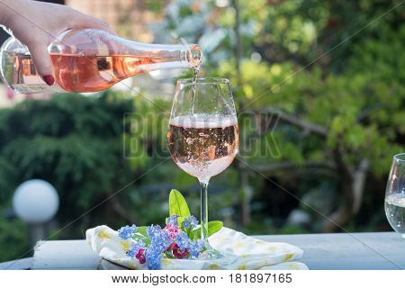 Waiter pouring a glas of cold rose wine outdoor terrase sunny day green garden background