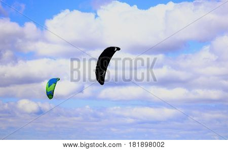 two parachutes against the blue sky and clouds
