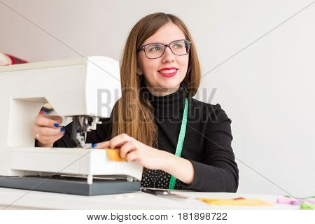 needlework and quilting in the workshop of a young woman, a tailor on white background - young smiling girl tailor working on a sewing machine and looks up away from the work