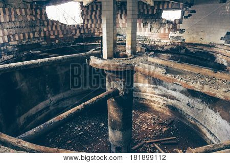 Inside an abandoned factory, a shop with a circular capacity and destroyed walls