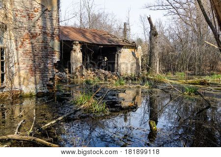 Old brick abandoned house with a ruined wall swamped by a swamp