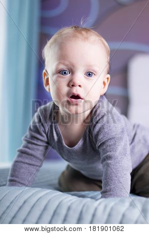 Surprised Open Mouthed Baby Boy Looking At Camera. Blue-eyed Infant Kid Indoor.