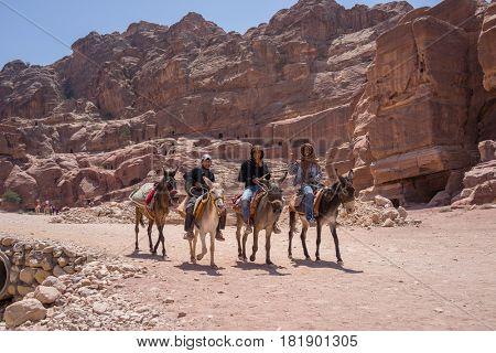 Tourists travellers visiting Petra in Jordan during summer vacation. Petra, Jordan - August 9, 2016