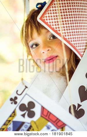 Portrait of little beautiful girl in the scenery of Alice in Wonderland with big game cards
