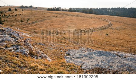 Split Rail Fence at sunrise above Lost Water Canyon in the Pryor Mountains range on the Montana Wyoming state line USA