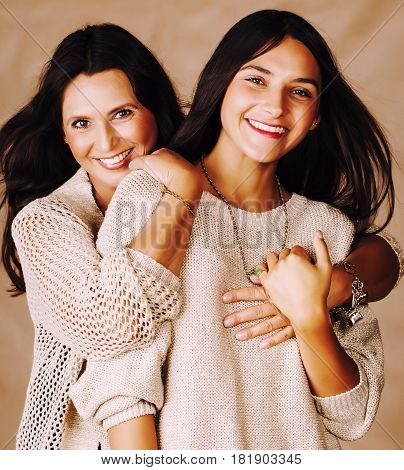 cute pretty teen daughter with mature mother hugging, fashion style brunette makeup close up tann mulattos together, warm colors close up