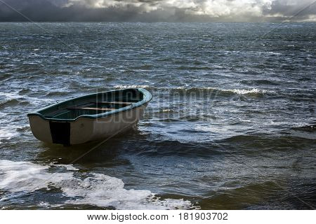 Empty rowboat floats lonely on the sea waves to the clouds at the wide horizon seascape with copy space in the water