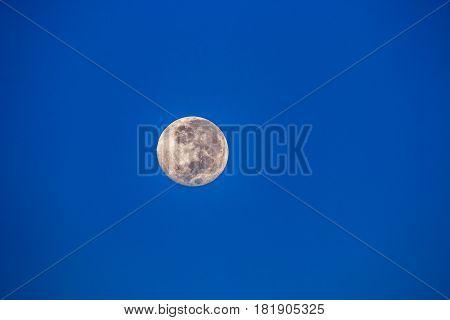 Full moon seen in the early morning in the Namibian desert.