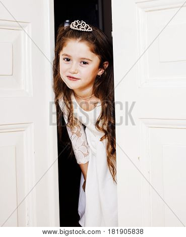 little cute girl at home, opening door well-dressed in white dress and tiara, adorable milk fairy teeth close up