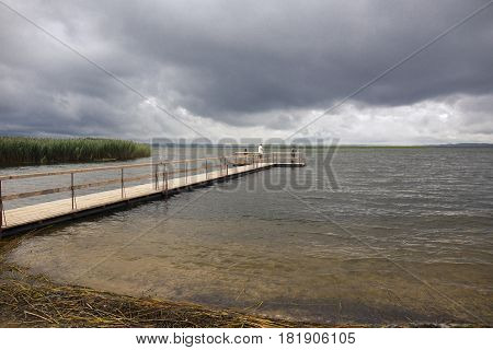 Dramatic landscape with wooden pier and fishermen on the lake