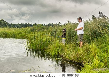 Father and little son fishing on grassy river shore