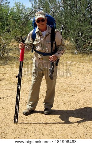 Senior hunter in sonora desert carrying rifle and pack
