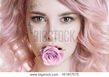 Colored hair. Beauty women portrait. half face of young curly woman with pink hair, perfect art make-up with glitter. Rose in her mouth. Studio