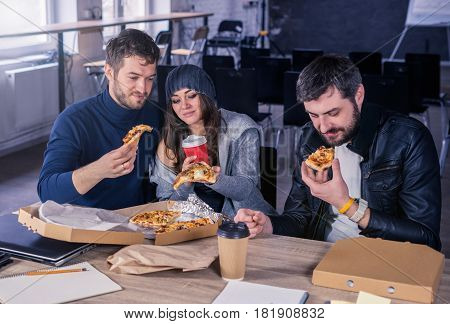 Business team eating pizza and drinking in office together. Everybody is holding pizza. Working environment with laptop, coffee, notepads and stationery.