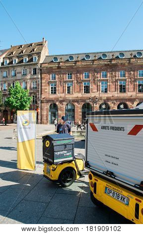 STRASBOURG FRANCE - JUN 24 2016: Man admiring fleet of Postal delivery electric cars and vans in a row in central Square Place Kleber early in the morning. La Poste is France's leading employer with a total workforce of 300000 working in postal shipping a