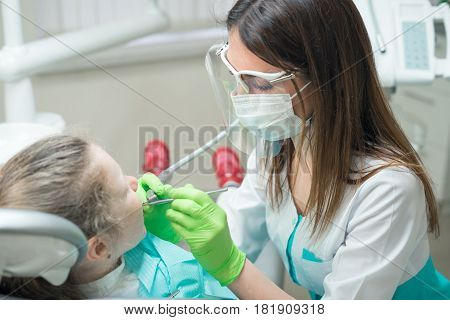 Closeup view of small cute girl in the dentist's chair. dentist in facemask treating child's teeth