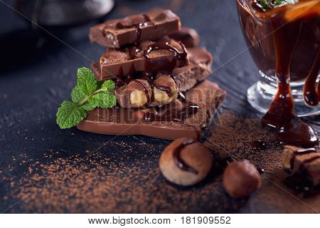 Homemade hazelnut spread or hot chocolate in glass bowl with nuts and chocolate bar. Cocoa powder nuts and chocolate background. Ingredients for cooking homemade chocolate sweets.