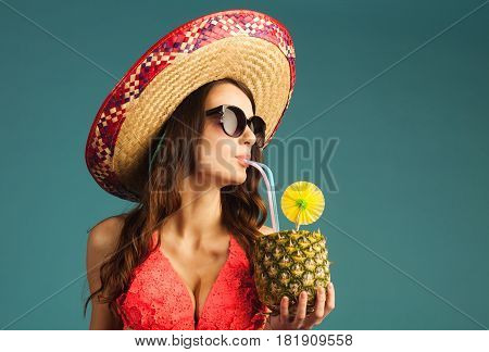 young beautiful woman in bikini sunglasses and sombrero drinking tropic cocktail isolated on blue background close-up