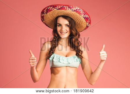 happy smiling woman on tropical vacation in bikini and hat with showing awesome gesture isolated on pink background