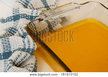 Liquid ghee in the glass baking dish on white background with white-blue towel