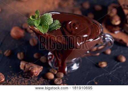 Homemade hazelnut spread or hot chocolate in glass bowl with nuts and chocolate bar. Cocoa powder nuts and chocolate background. Confectionery and sweets concept.