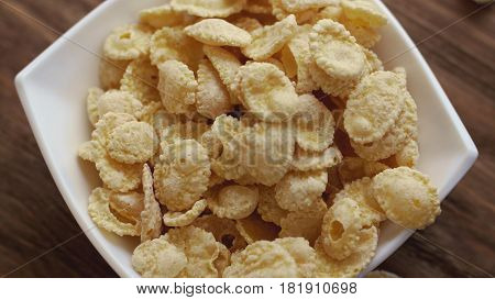 Fresh yellow corn flakes in white bowl. Concept of breakfast.