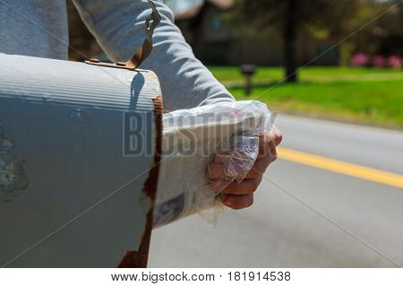 Close-up Of Man's Hand Taking Letter From Mailbox Outside House Man takes mail from the mail box