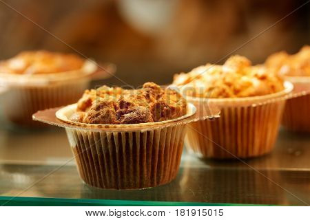Sweet muffin cupcakes in glass display at the bakery. Selective focus.