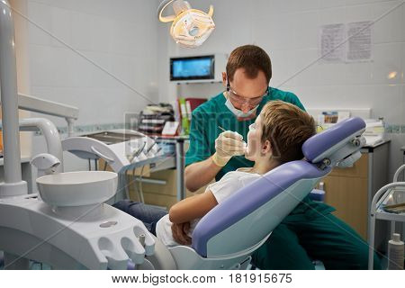 MOSCOW, RUSSIA - OCT 19, 2016: Dentist examines mouth and teeth of boy sitting in armchair in Children Medical Center Sanare for children of all ages from birth to 17 years old.