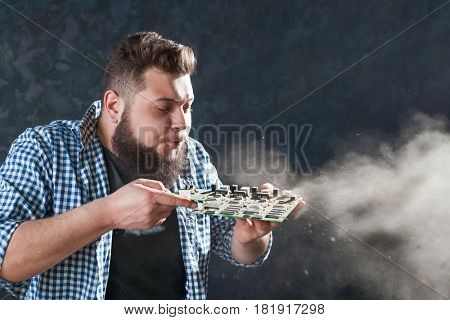 Male engineer blows off the dust from motherboard