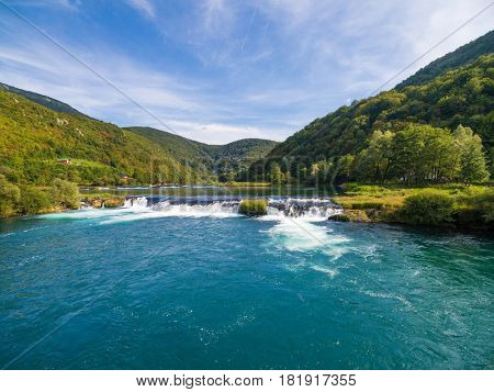 Aerial view of  Una river waterfall surrounded by forest and hills, Bosnia and Herzegovina.